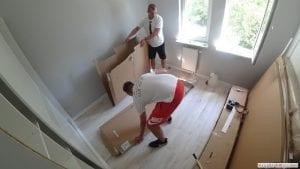 Monterzy przygotowują miejsce w pomieszczeniu do składania i skręcania łóżka